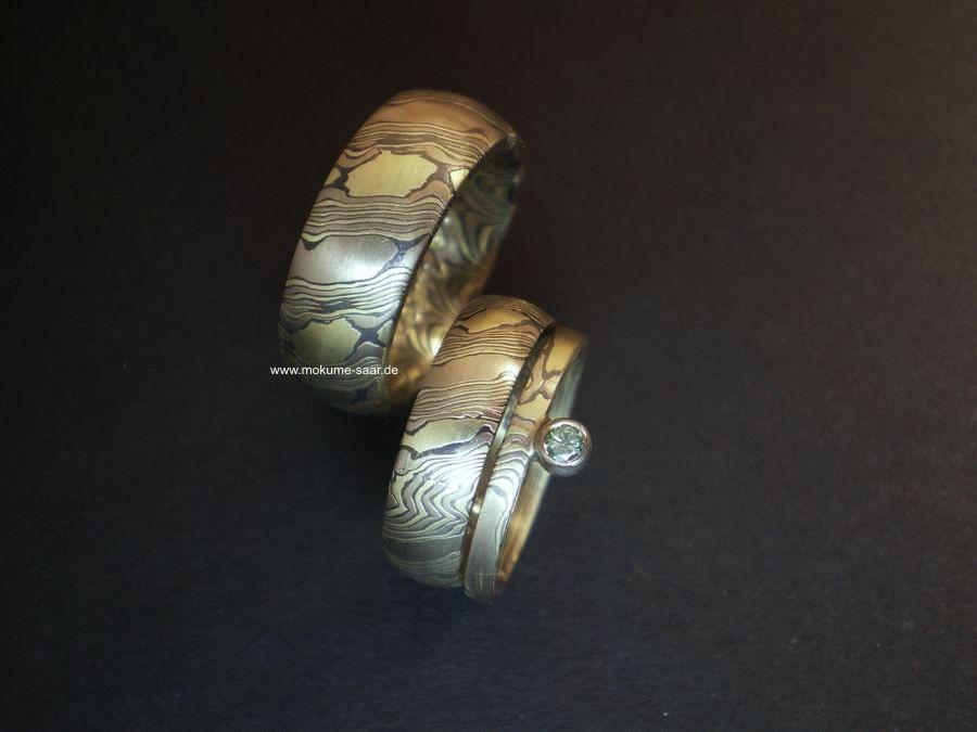 Breite Mokume Gane Eheringe mit oxidiertem Silber und Beisteckring mit Brillant
