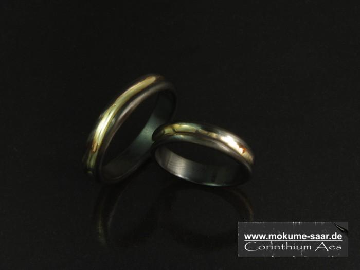 2 schwarze Ringe mit Goldeinlage