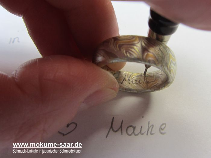 In einen Mokume Gane Ring wird ein Name mit Bleistift eingezeichnet