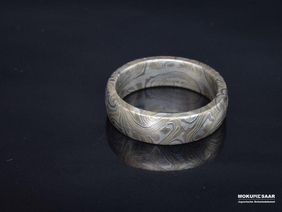 Besonders gemusterter Mokume Gane Ring liegend auf schwarzem Untergrund
