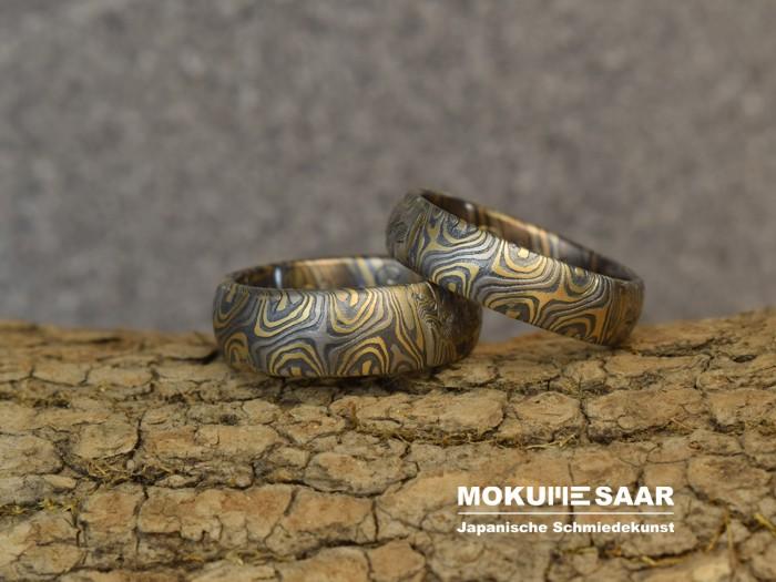 Zwei Mokume Gane Eheringe mit Sternenmuster fugenlos liegen auf einem Holzstück mit Baumrinde