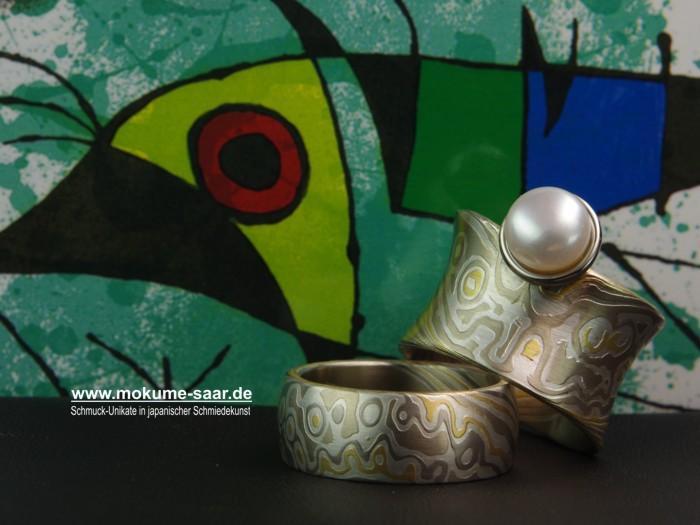 Breite Mokume Gane Eheringe mit einem besonderen Muster, der Damenring mit Perle, liegen vor einem bunten Hintergrund