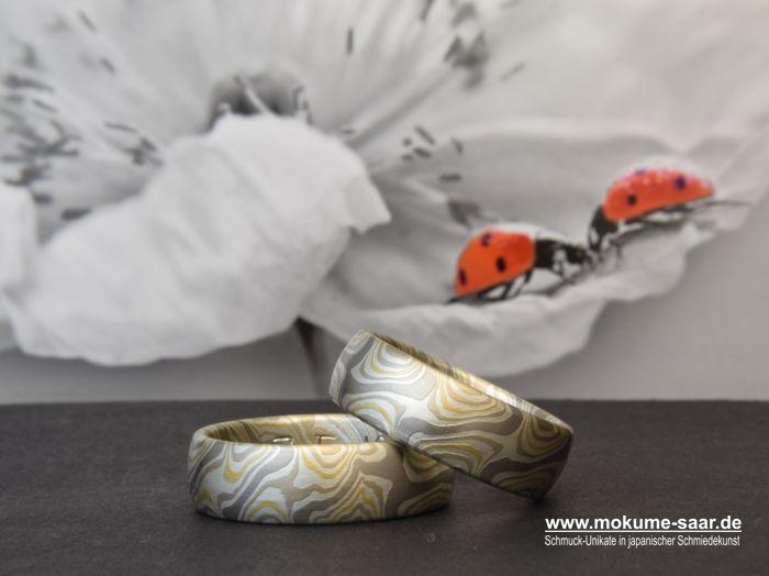 Zwei MOkume Gane Eheringe mit Sternenmuster liegen vor einem Bild mit Blüte und zwei Marienkäfern