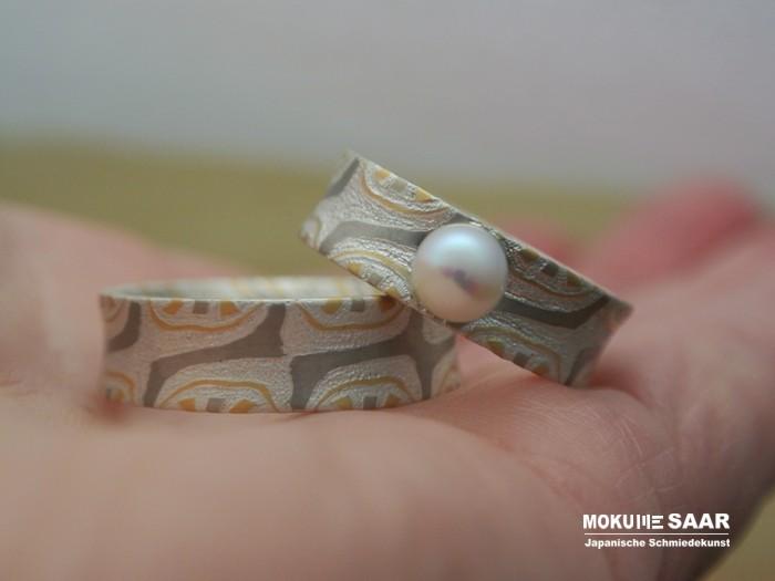 Ein Paar Mokume Gane Eheringe mit speziellem Muster und einer Perle liegen auf einer Handfläche