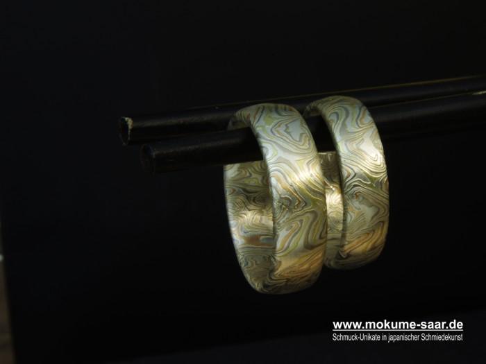 Zwei japanisch geschmiedete Trauringe mit besonderem Muster hängen an Essstäbchen