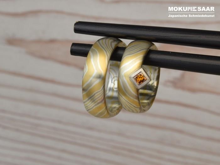 2 Mokume Gane Eheringe mit Wellenmuster und einem orangefarbenen Brillanten in quadratischer Weißgold-Fassung hängen an chinesischen Essstäbchen