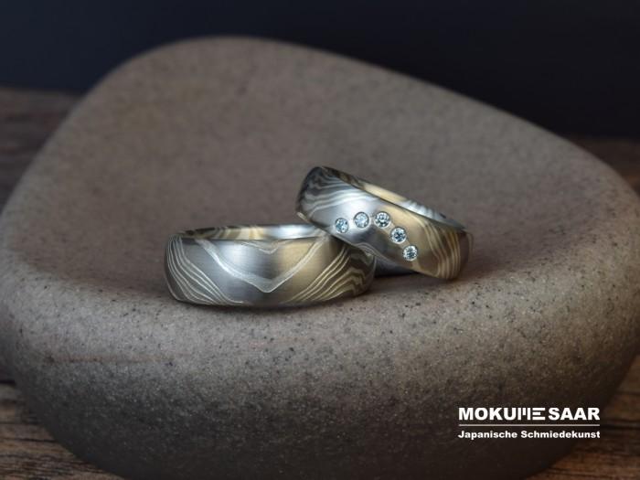 Ein Paar Mokume Gane Trauringe mit Wellenmuster aus Weißgold und Silber, Damenring mit 5 blauen Brillanten