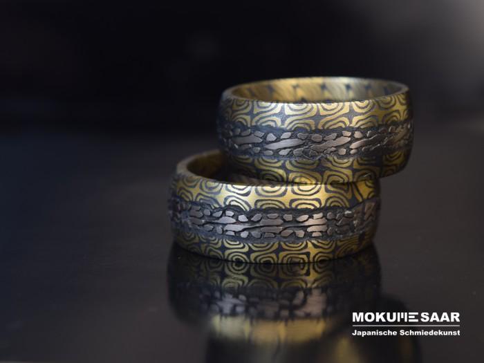Zwei Eheringe mit einzigartiger Mokume Gane Musterung liegen aufeinander gestapelt auf einem schwarzglänzenden Untergrund