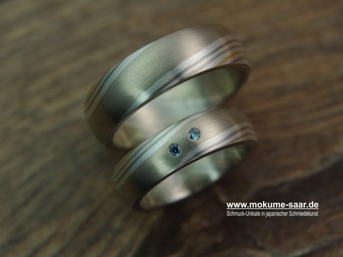 Ein großer runder Anhänger an einer Goldkette und mit Brillant in der Mitte lehnt an einer Schale, daneben liegt ein breiter Mokume-Gane Ring