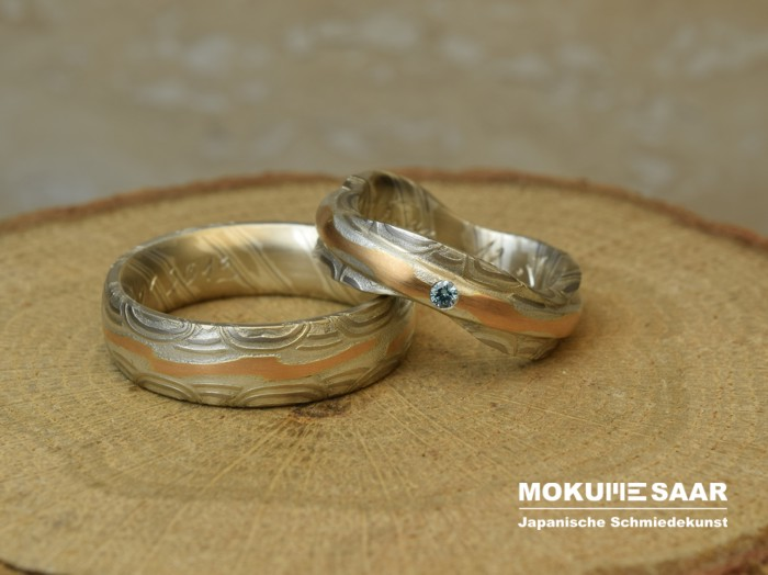 Auf einem runden Holzklotz liegen zwei Mokume Gane Eheringe aus Weißgold, Rotgold und Silber, der Damenring ist mit einem blauen Brillant besetzt.