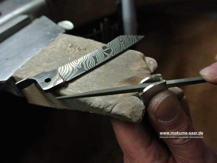 Damaszener Messerklinge auf einem Feilnagel, Hände, die die Griffschale feilen