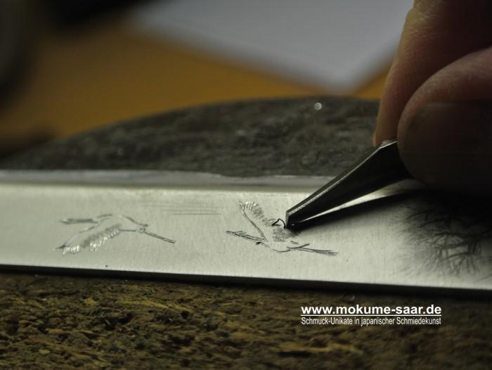 Ein Stichel graviert einen Kranich und ein Span wird herausgeschnitten