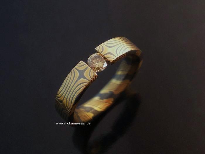 Mokume Gane Ring mit Sternenmuster aus Gold und oxidiertem Silber mit gespanntem Brillant
